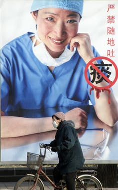 A woman on a bicycle and wearing a mask rides past a billboard showing a picture of a health worker.
