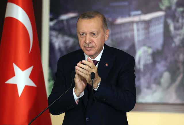 Turkey's Recep Tayyip Erdogan applauds as he stands behind a microphone and beside the Turkish flag.