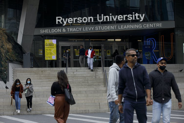 People walk in front of a Ryerson University building.