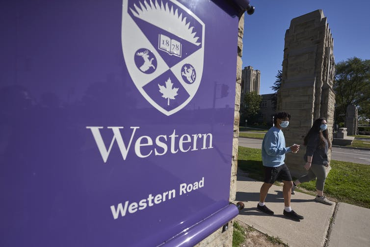 Students walk through a gate at Western University.