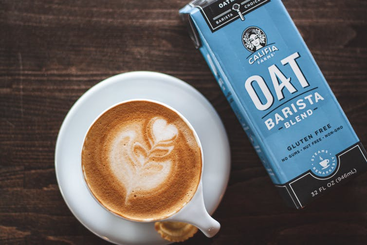 Oat milk carton beside a coffee