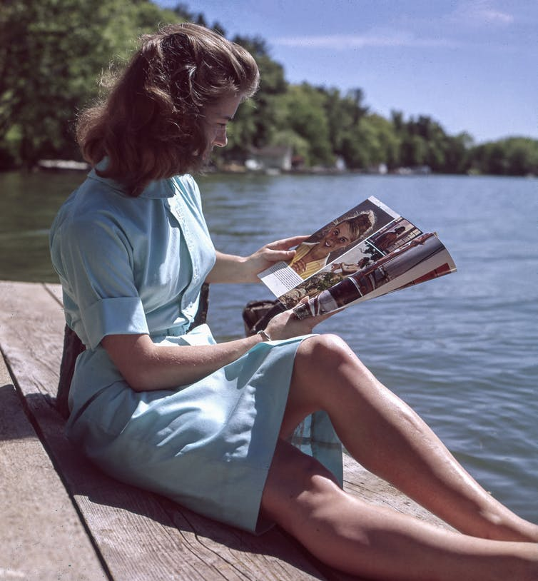 A 1950s woman reads a magazine