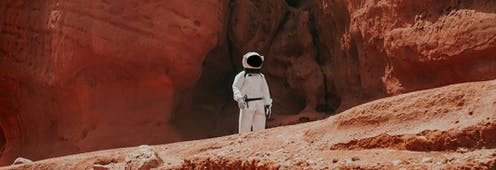 Una persona con traje de astronauta en un paisaje desértico.