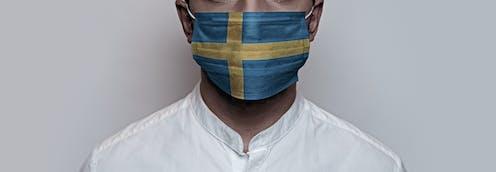 Un hombre con camisa blanca y mascarilla ilustrada con la bandera sueca