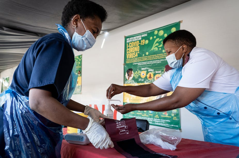 Nurses sanitise their hands and their tools after screening a patient in Johannesburg, South Africa.