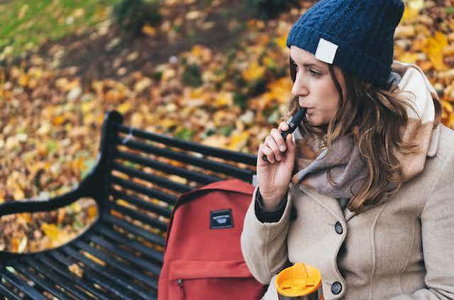 Woman sitting on park bench smoking an e-cigarette