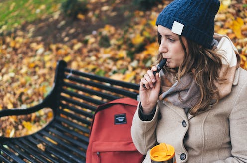 Woman sitting on park bench smoking an e-cigarette