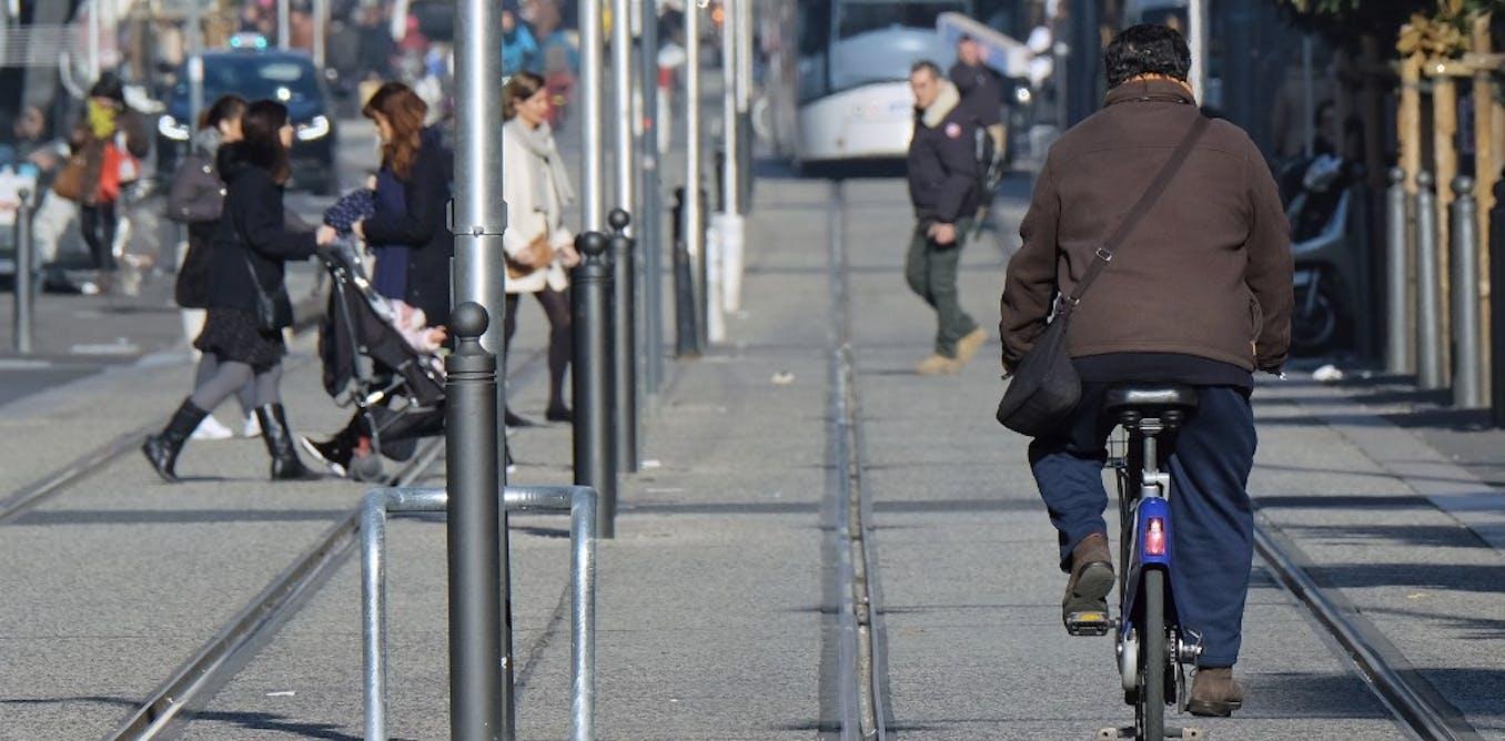 Un homme conduit un vélo à côté d'une ligne de tramway de la ville, le 24 janvier 2017, à Marseille.       Boris Horvat/Afp