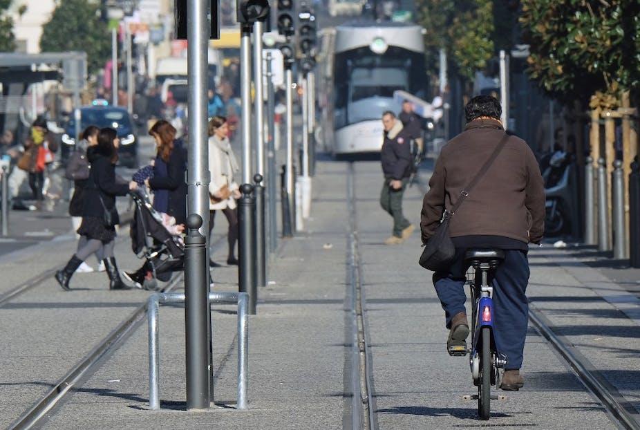 Un homme conduit un vélo à côté d'une ligne de tramway de la ville, le 24 janvier 2017, à Marseille.