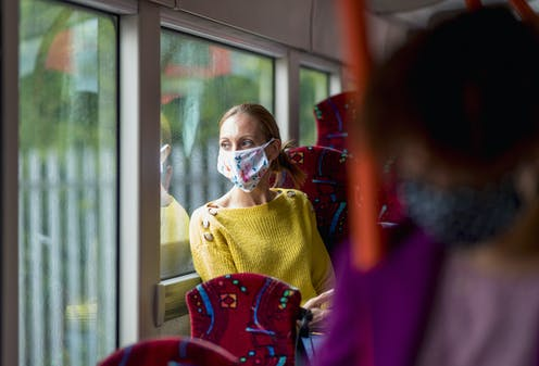 masked woman looks out bus window