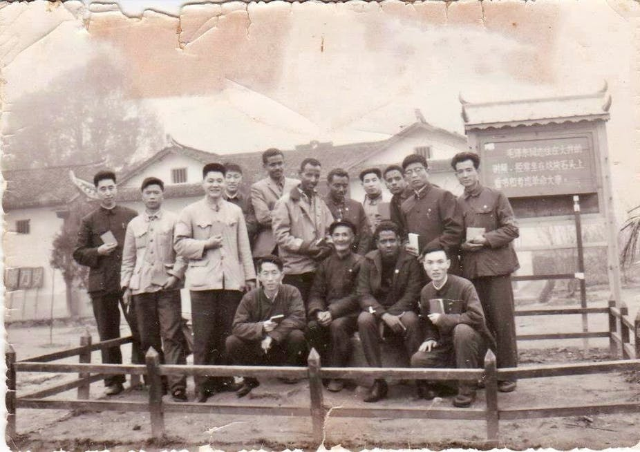 Group of men outdoors, backdrop of Chinese style buildings, black and white vintage photo
