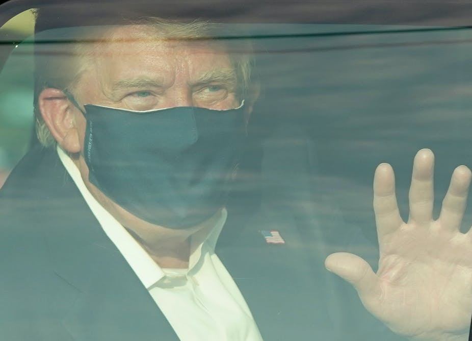 President Trump waves to supporters as he drives drives past them in a motorcade outside of Walter Reed Medical Center.