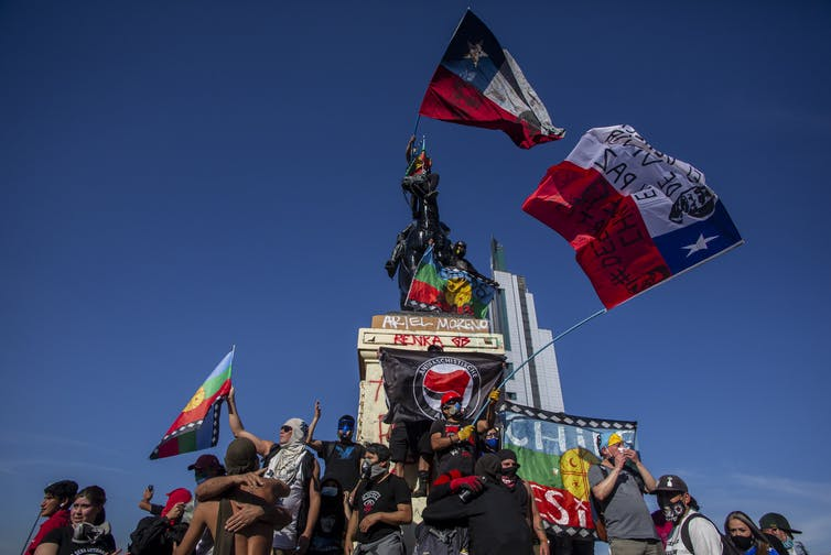 Chileans wave flags while standing on a graffiti-covered national monument.