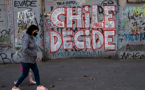 A woman in a face mask walks past a graffiti reading Chile Decides