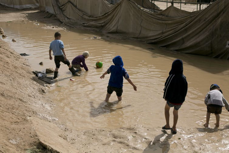Five children playing in a large mud puddle