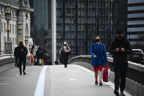 People wearing masks crossing Westminster Bridge, London.