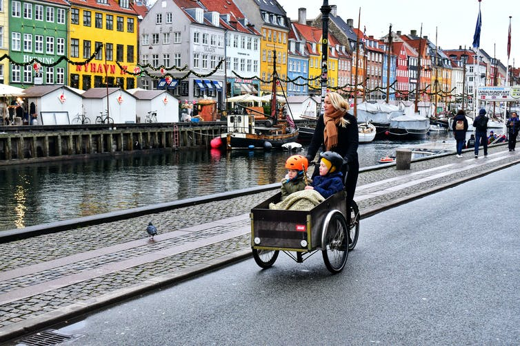 A woman takes her two kids in a cargo bike, in Copenhagen.