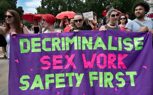 Protest banner: 'decriminalise sex work, safety first'