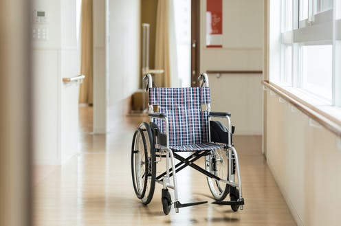 A wheelchair sits in the corridor of a nursing home.