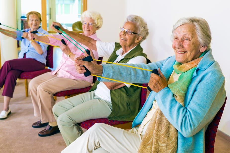 Elderly women exercising with resistance bands.
