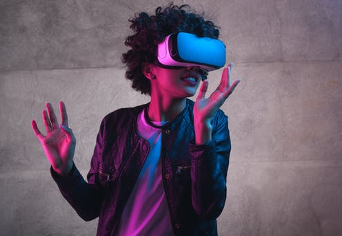 Cheerful girl with hands up wearing the virtual reality goggles