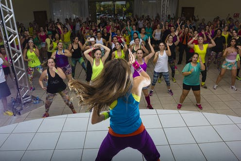 Woman on stage leads large dance class