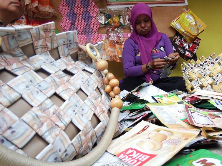 Seorang perempuan sedang memilin kantong plastik dikelilingi tas daur ulang dari kemasan.