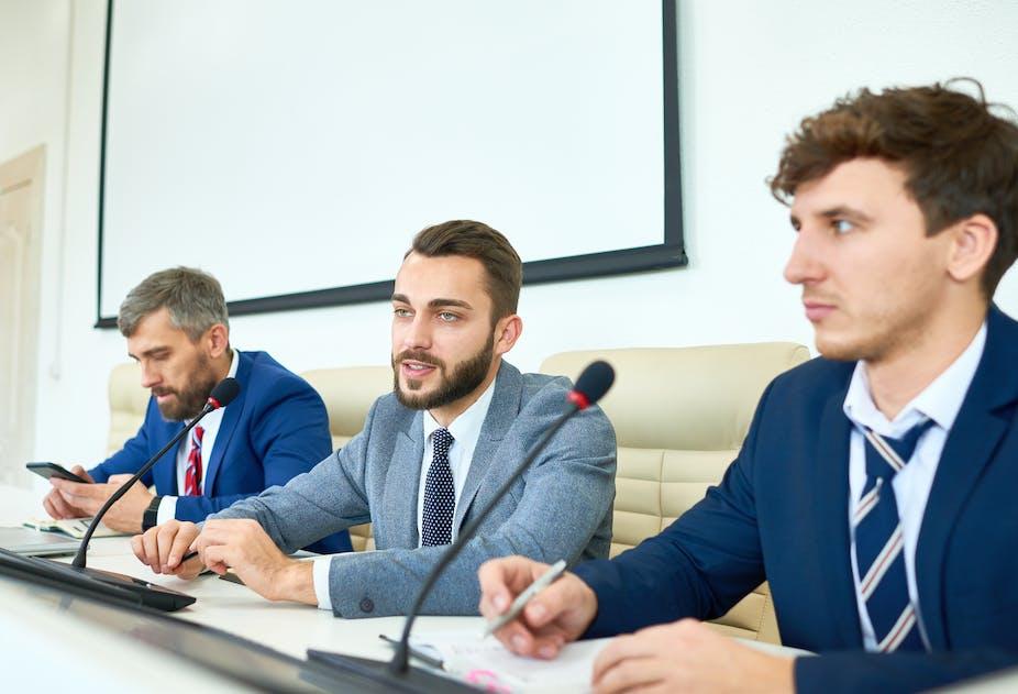 Three men in suits sat in front of microphones
