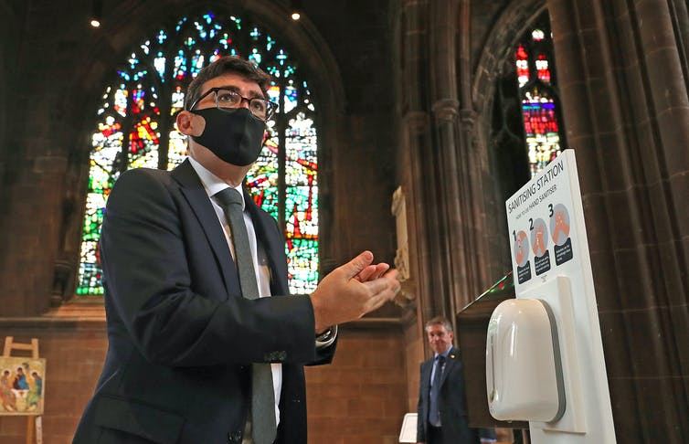 Andy Burnham santising his hands at a memorial service.