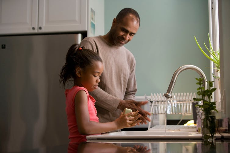 A man and his daughter wash dishes together.