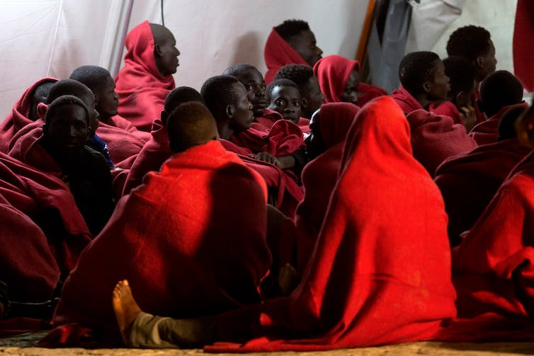 A group of people wearing red sit huddled on the floor.