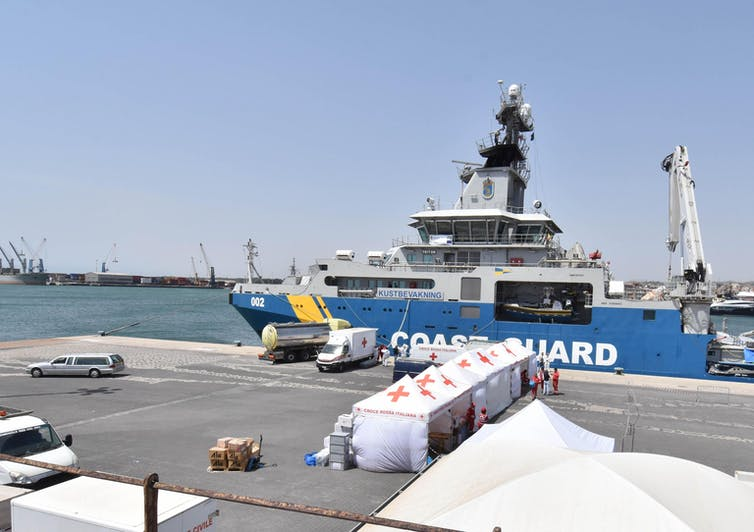 A coast guard ship in port next to red cross tents.