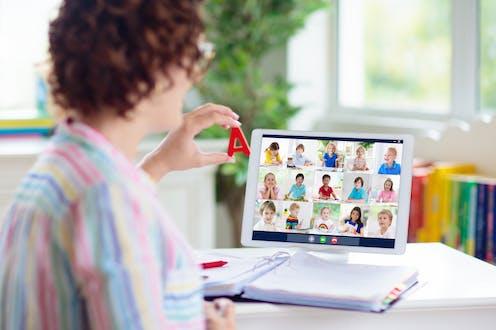 Una maestra dando clase en línea a quince niños