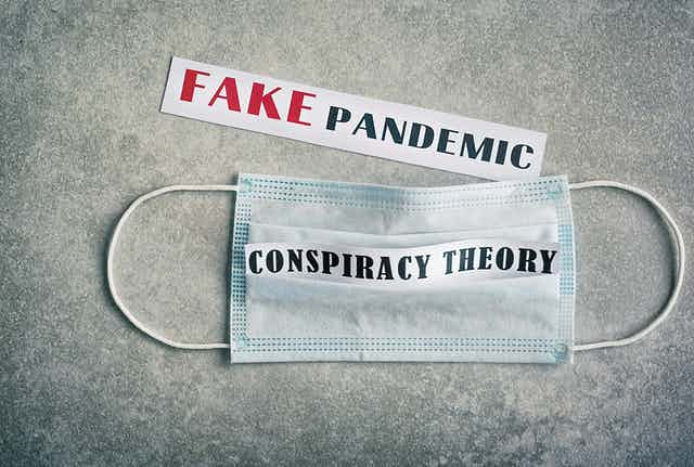 A face mask with the words 'conspiracy theory' written on
