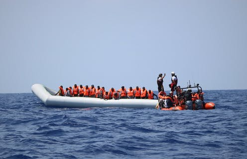 A group of migrants in orange life jackets in a rescue boat in the Mediterranean Sea.