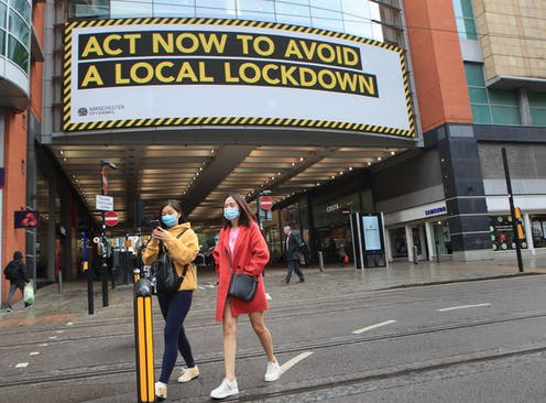 Shoppers walking in front of a sign warning about the potential for a local lockdown.