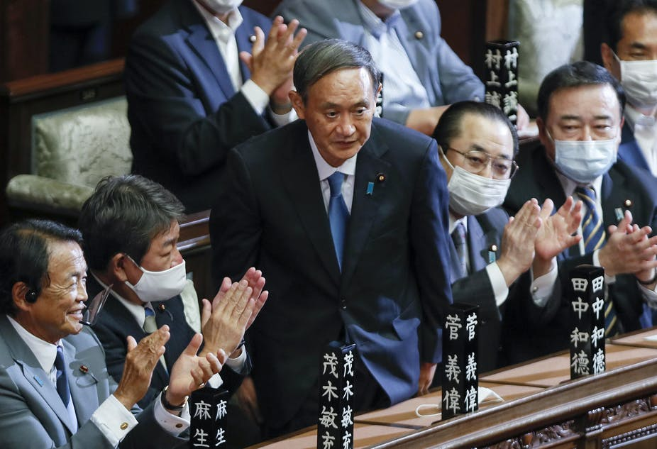 Yoshihide Suga stands up in parliament surrounded by seated men clapping.
