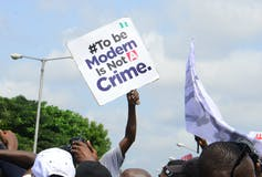 A man holds up a square white placard reading, '#To be Modern is Not A Crime'
