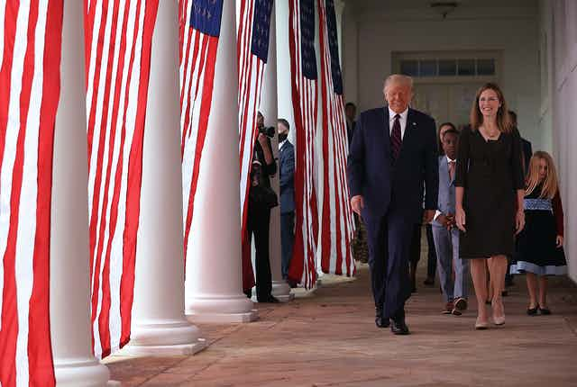 Trump and Barrett walk down a colonnade adorned with American flags