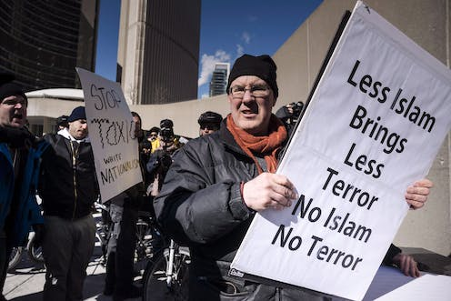 A white man holds a sign saying LESS ISLAM BRINGS LESS TERROR NO ISLAM NO TERROR