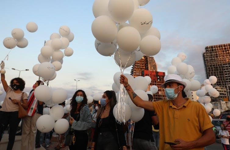 Des Libanais se rassemblent pour lâcher des ballons blancs près du port de Beyrouth