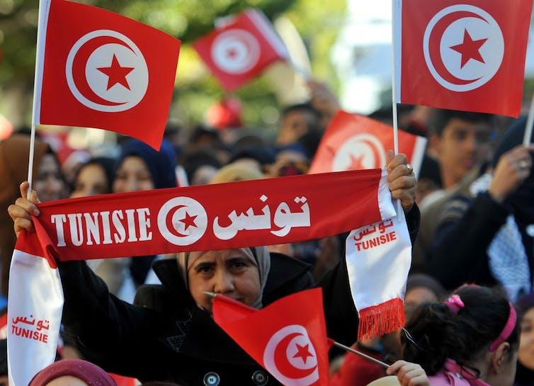Une femme tient le drapeau national tunisien