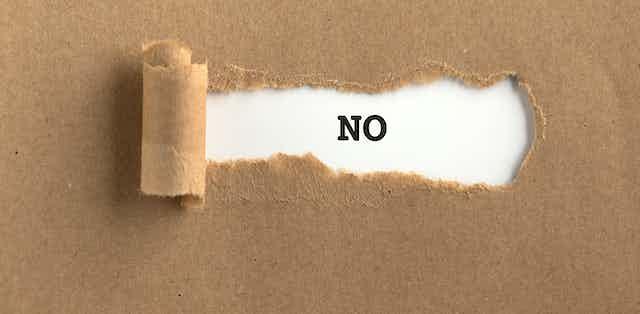 Un NO de imprenta tras un papel rasgado