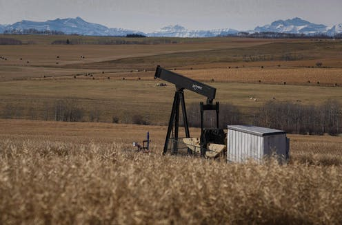 A pumpjack on a farmer's field with mountains in the background