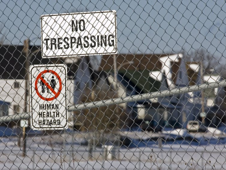 Chain-link fence with 'no trespassing' and 'human health hazard' signs