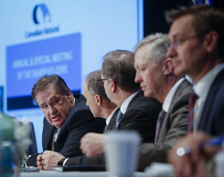 A panel of men at a conference