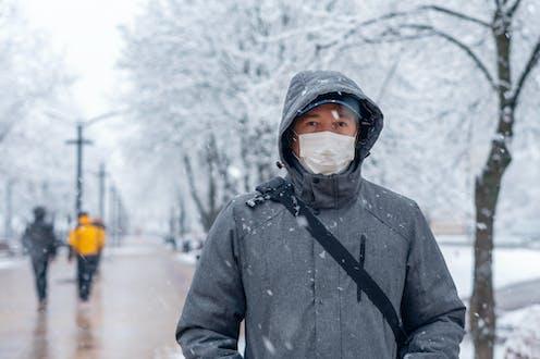 Un hombre abrigado y con mascarilla pasea por un parque nevado.