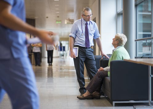 Standing doctor speaks to seated woman