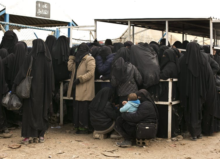 Women in black niqabs and hijabs waiting together in a crowd