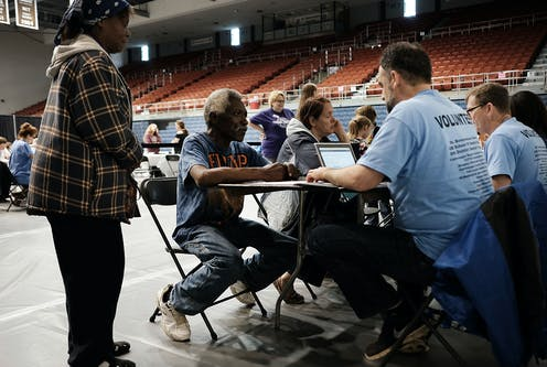 a health-care volunteer provdies services to a resident at a health camp in an indoor arena.
